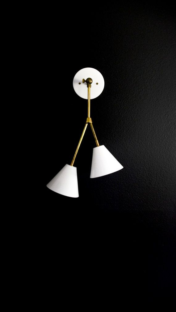 Constructed of solid unfinished brass materials, the adjustable branching double shaded tilting sconce is a fixture that can be mounted on the