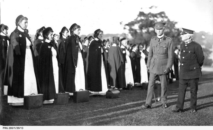 Army nurses on parade during an inspection by two male officers, one identified as Colonel Wallace, in Sydney, New South Wales; the nurses, who stand with their small hand equipment cases on the ground in front of them, are wearing long cloaks over their uniforms and hats tied under their chins