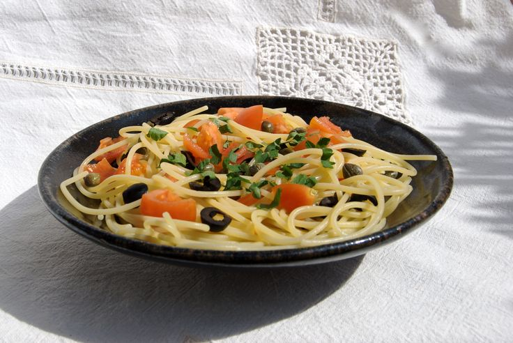 Spaghetti Crudaiola. Chop garlic, anchovy and parsley. Cut black olives and tomatoes into small pieces. Cook spaghetti 3 minutes less than indicated. Drain the pasta keeping one cup of its cooking water aside. Add extra virgin olive oil to a pan and stir fry garlic and anchovy. Don't let it burn. Then add olives, tomatoes and capers and let simmer at low heat for a few minutes. Now add pasta and its water and cook for 3 min. Salt to taste and add the chopped parsley.