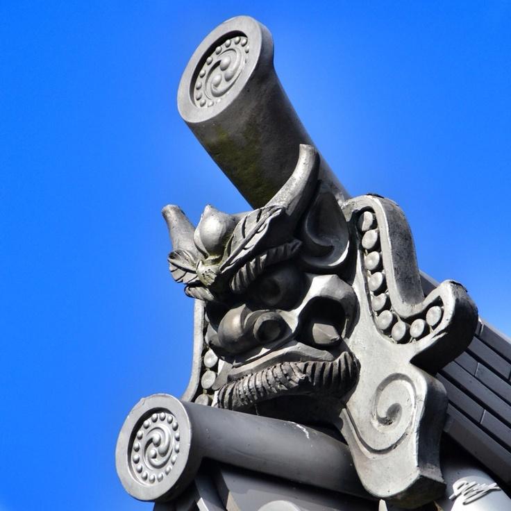 2012/12/18 Photo Diary:  Onigawara  京都の風景。 厄除を込めて屋根の上に設置される「鬼瓦」。 その昔、中東で入口の上にメドゥーサを厄除けとして設置していた文化が シルクロードを経て、中国から日本に伝播されたとのこと。  鬼は、節分などで退治の対象となるほど嫌がれるのに、 それを使ってしまう、 いわば、毒を以て毒を制す的な発想は、深い。  The thing on the leaf of temple.  / Photo / NIKON D3100 / Object / Kyoto