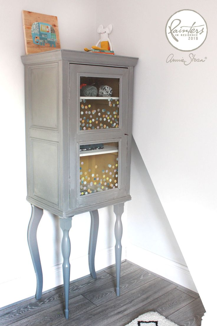Nursery wardrobe hack by Painter in Residence Hester van Overbeek! She has upcycled this display cabinet by adding IKEA table legs and painting in Chalk Paint® in a mix of Paris Grey and Graphite. The windows are decorated with confetti polka dots of Chalk Paint® in yellows, blues, and oranges.