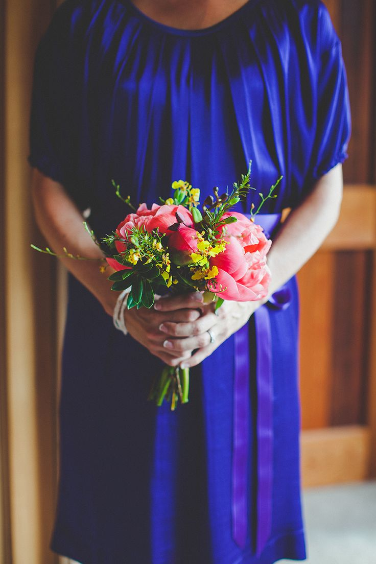 Pink peonies and yellow oncidium orchids pop against the purple in the girls dresses. Photo: Bayly and Moore