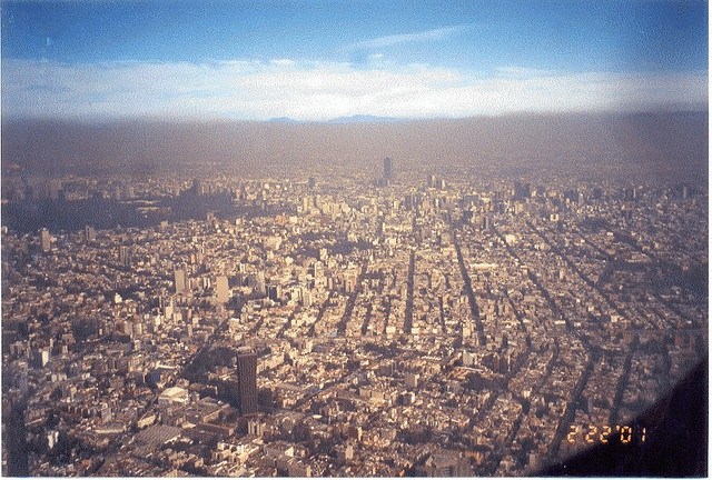 """A view from the window of an airplane on approach to the Mexico City Airport. Note the difference between the color of the air above and below eye level. This is air pollution at its """"best or worst"""" and is always present at this city.    On the way to Cuernevaca"""