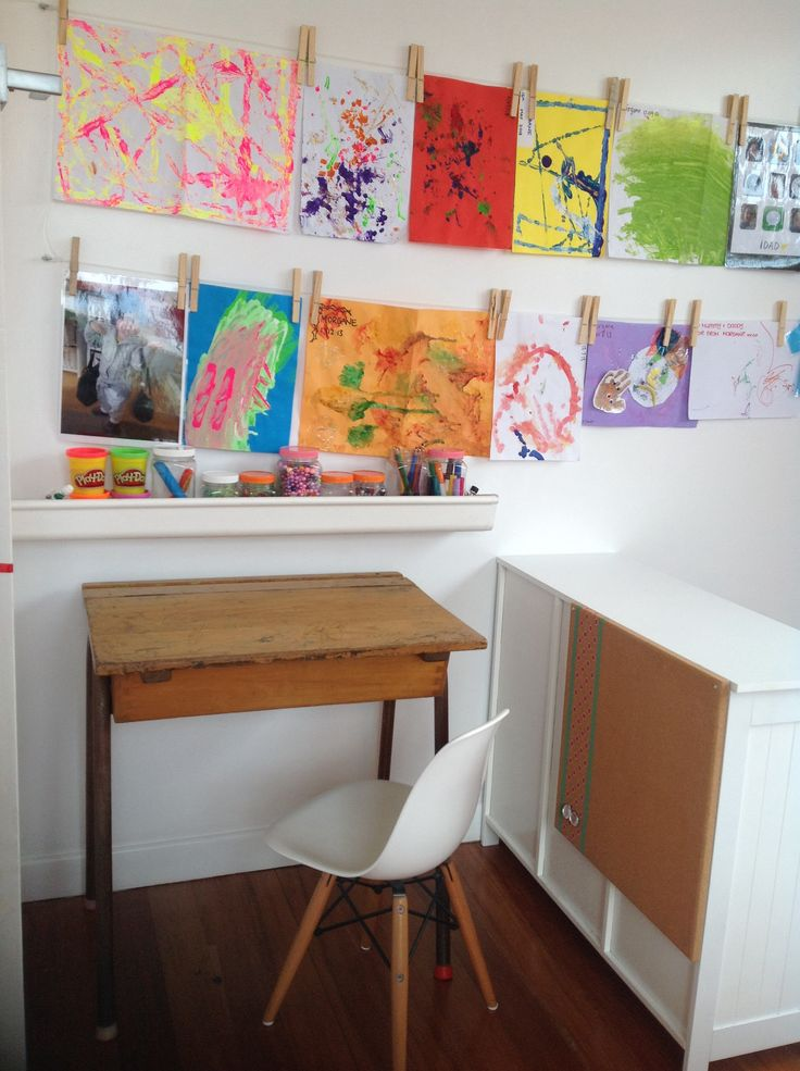Creative corner with wooden clothes pegs on fishing line to hang all the creations. Vintage old primary school desk and white replica Eames chair...