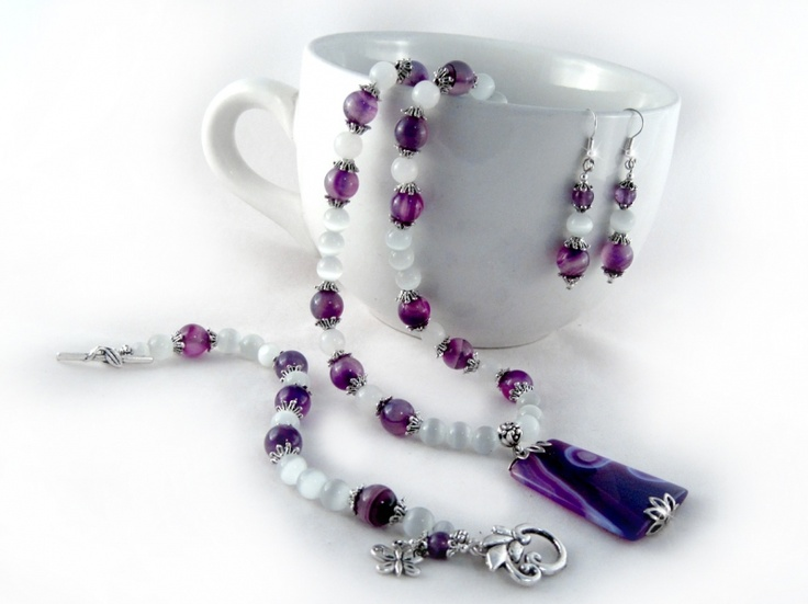 Violetta jewelry Set II $46.00 Purple striped Onyx, purple striped agate, white Cat's Eye beads, and Tibet silver are combined together for a stylish look. The necklace and the bracelet are strung onto tigers tail wire for strength, durability and drape. Finished off with an ornamental leaf shaped toggle clasp. The earrings are strung onto silver plated wire.