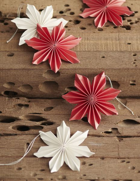 Pearlized red and white paper is folded and cut to create beautiful poinsettia flower ornaments. Each lightweight bloom hangs from slender cotton thread.  Dimen