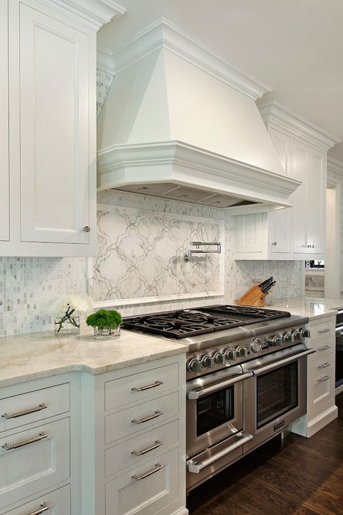 Gorgeous kitchen with stainless steel stove with double ovens paired with a swing arm pot filler framed by a white marble arabesque backsplash under a white stove hood. The stove is framed by white cabinets accented with brushed nickel cabinet pulls alongside a Taj Mahal Quartzite countertop with marble mosaic backsplash.