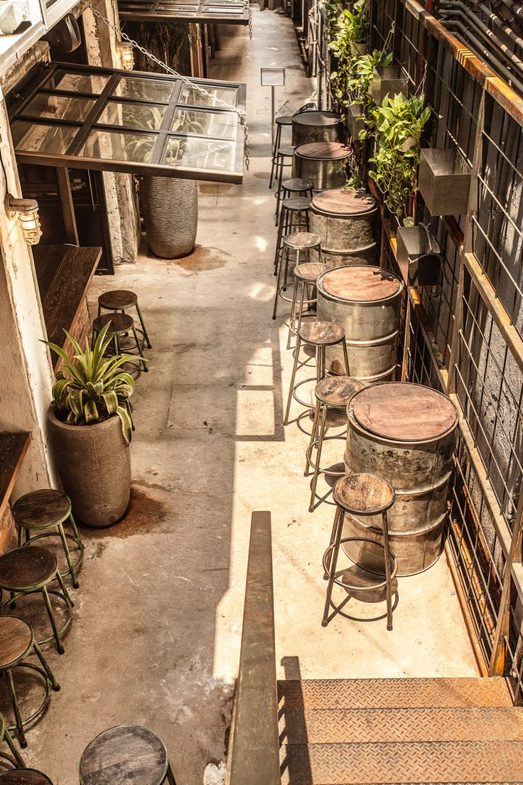 Задний двор ресторана с бочками-столами и барными стульями.