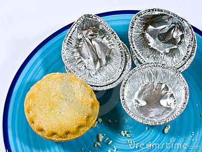 A closeup a mince pie with empty pie containers and a few crumbs on a pottery plate