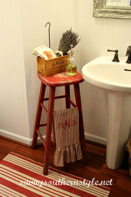 old stool in the powder room that is used as a place for hand towels and soap