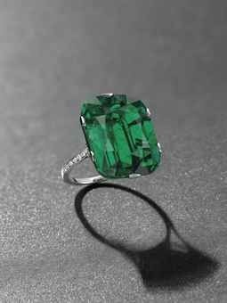 An exceptional emerald and diamond ring. Photo Christie's Image Ltd 2013 Set with a cushion-shaped emerald, weighing approximately 23.28 carats, to the diamond line shoulders, mounted in platinum, ring size 6.