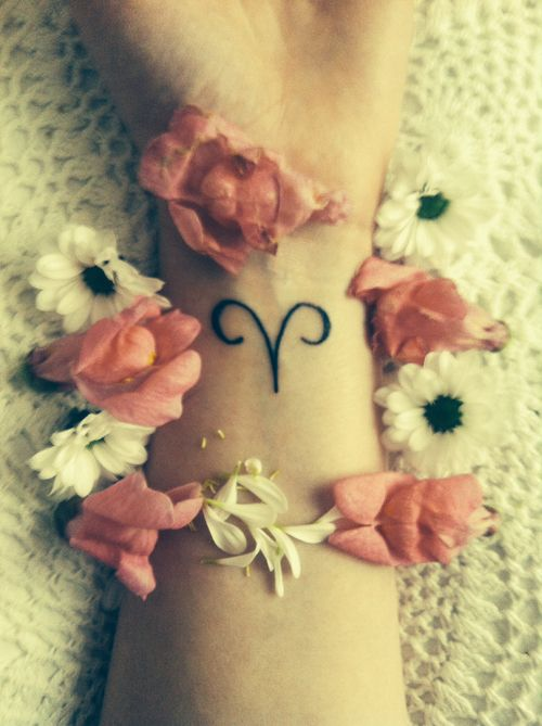small Aries sign tattoo with sweetness and daisies circled around
