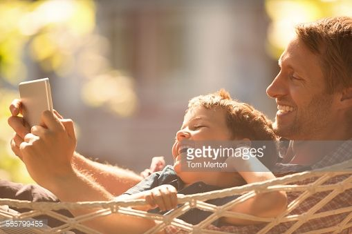 Stock Photo : Father and son using digital tablet in hammock