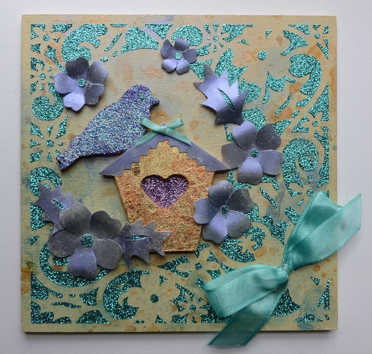 Front of MDF 'Birdhouse' Wall Hanging.   Imagination Craft's. _ Spring is here stencil.  Flower frame border stencil.  Purple velvet & Jade sea Detail Sparkle.  Mica powders.  White shimmer Detail Sparkle.  Golden Glow gilding flakes.  Gilding glue.  Metal spatula.  Magi-bond glue.  Spritzer bottle.  Limestone MDF paint.  MDF Birdhouse charm set.  Turquoise ribbon.  June 2013.