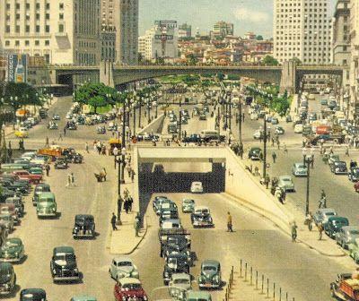 A imagem acima é muito rara. Possa não acreditar, mas ela é dos anos 50, e ainda assim é colorida. Ela mostra o Vale do Anhangabaú, em São Paulo-SP. Sua tarefa é identificar vários carros!