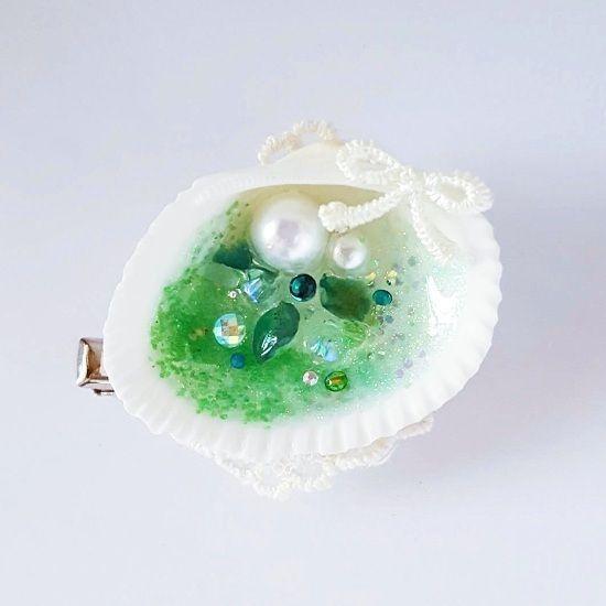 天然の貝殻をフレームにしたブローチ。ラメ、パール、スワロフスキーストーン、天然石など、人魚姫の宝物を貝殻の中に。グリーンメノウというパワーストーンも使用しました。明るい未来を引き寄せるという意味を持ち、マイナスの考えを明るく変えるのを助けてくれます。バッグや帽子など、夏の小物と合わせてコーディネートのアクセントに。いつまでも続く美しい世界を連れて、お出かけをお楽しみください。●カラー:緑●サイズ:クリップの長さ:4.5㎝、貝殻のサイズ:縦3㎝、横4.3㎝●素材:貝殻、レジン、パール、スワロフスキー、グリッターラメ、レース●注意事項:貝殻は天然素材を使用しているため、個体差や多少の汚れ、欠けがある場合がございます。ラメは見る角度によって輝きが異なって見えます。強く引っ張ったり、ひっかけるとパーツが取れてしまう恐れがございますのでご注意ください。●作家名:パルティア貝殻入り/アクセサリー/ 海の水/マーメイド/涼やか/小物/ 天然貝/シェル/透明感と光沢/本物の貝殻/貝殻モチーフ/綺麗/クリア感/夏/ツヤと輝き…