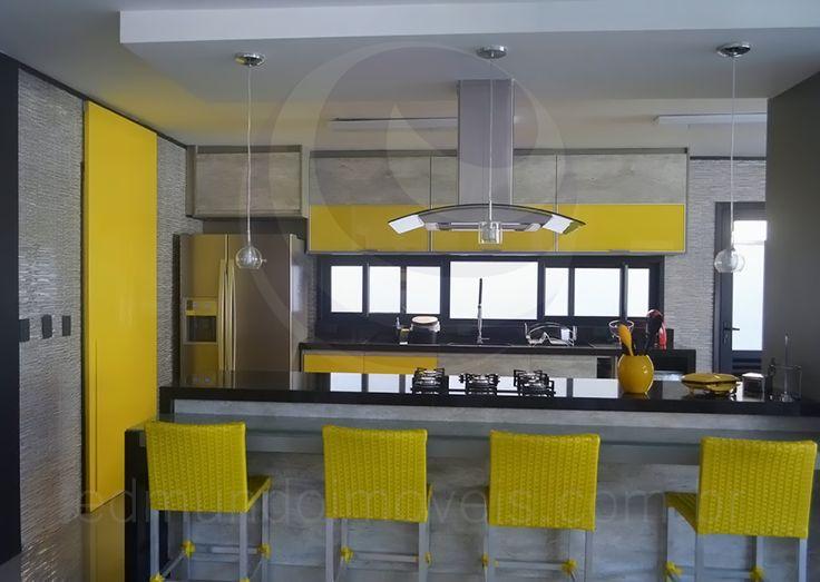 Na cozinha americana, tons monocromáticos dominam o décor com superfícies em tons de cinza, como a bancada em granito e o balcão em mármore. Cadeiras altas com encosto em fibra amarela dão uma tônica alegre ao ambiente.