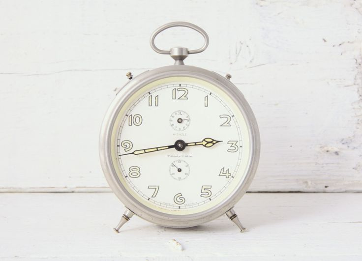 Tam-Tam alarm clock, made in Germany circa 1930's. it Has all the hallmarks of the Art Deco era. With its round Chrome body gently leaning back on attractively detailed feet and stand. With a carry handle on the top, with different functions.(afterglowretro.com,2013)