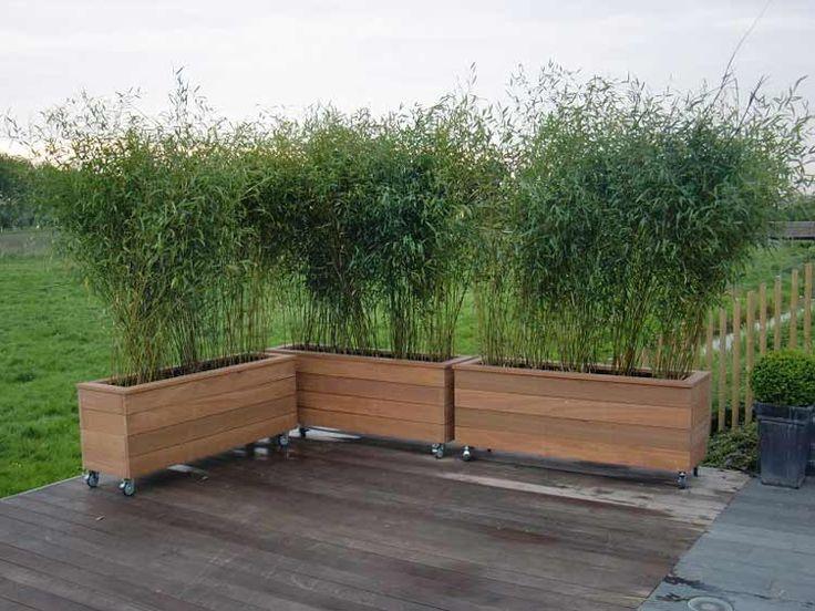 hardhouten plantenbakken op wielen met bamboe als afscherming steiger
