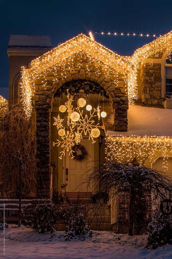 Collection of snowflake lights in different sizes and shapes hanging above the front entry with starlight spheres! This is a gorgeous Christmas porch decoration idea!
