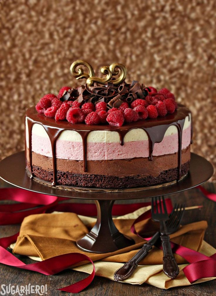 A fudge brownie base supports three layers of chocolate, raspberry, and vanilla mousse. And yes: That's molten chocolate drizzled over the cake and a bundle of fresh raspberries nestled on top.