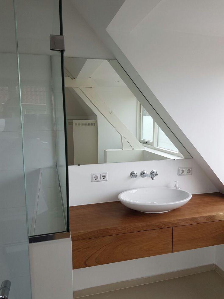 Deze spiegel op maat is door ons gemeten en geplaatst. De spiegel dient als afdekking van een achterliggende elektrokast die bereikbaar moet blijven. Door de schuine zijde past de spiegel precies tussen het douche gedeelte en de dakspant.