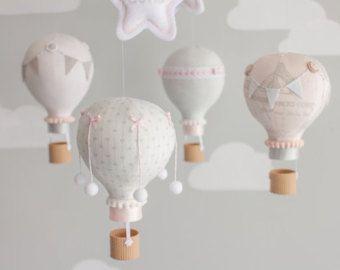Bebé rosa y blanco móvil de pequeños globos de aire caliente para una decoración de dormitorio tema viaje whimsical.  Las fotografías muestran a 5 globos de aire caliente flotando las nubes puffy bajo dos. Cada globo es hecho a mano de varias telas coordinación y adornado con banderas diferentes del empavesado, panaderos de la guita, botones, pompones y canastitas, impresos con tecnología 3D, le dan un aspecto real de mimbre. Cuelgan de un móvil de madera con dos cadenas de banderas pequeñas…