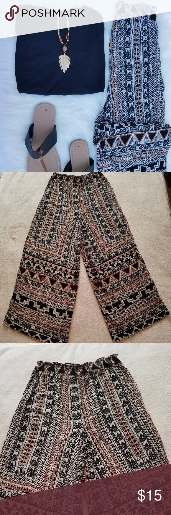 Angie Boho/Tribal Aztec Print Wide-Leg Pants Angie lightweight boho/tribal Aztec print wide-leg pants w/elastic waistband. Pants are black, off-white, & copper. No pockets.   Size: L Material: 100% rayon  Measurements [Approximately]: Waistband to hem: 39.25 inches Waistband width: 13 inches, loose & 21 inches, stretched Hip width: 21.25 inches Inseam: 26.5 inches Hem opening: 13.5 inches  *Selling ONLY pants* Angie Pants Wide Leg