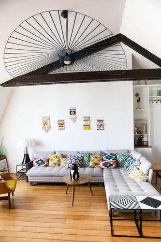 Un canapé dangle des jolis coussins et des luminaires design associés à des