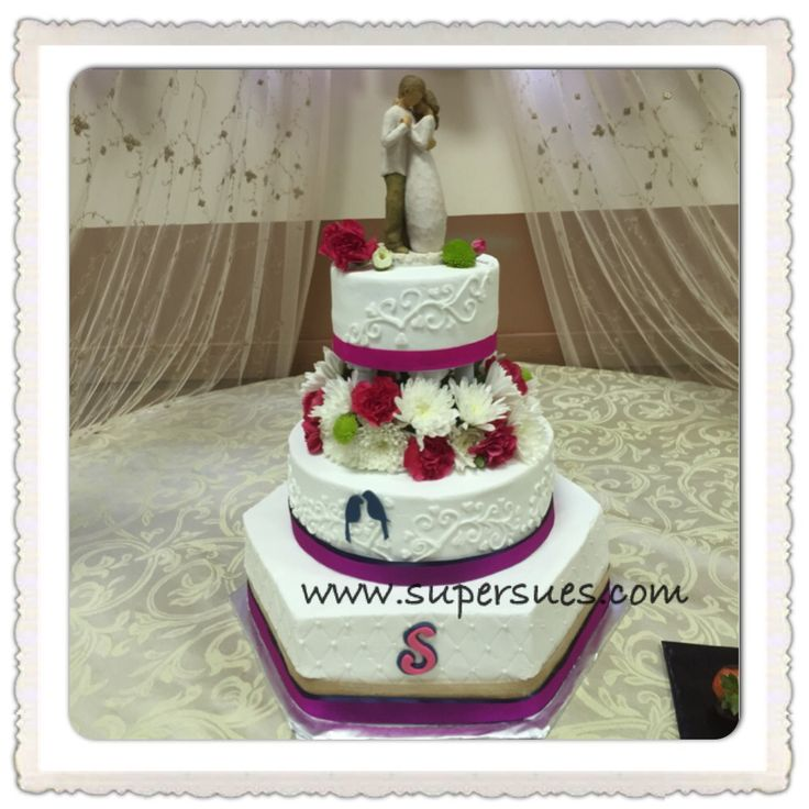 """This fun wedding cake is a 15"""" hexagon, 10"""" round and an elevated 6"""" tier with fresh flowers. There is heart swirl piping and 2 navy blue fondant love birds.  Www.supersues.com"""
