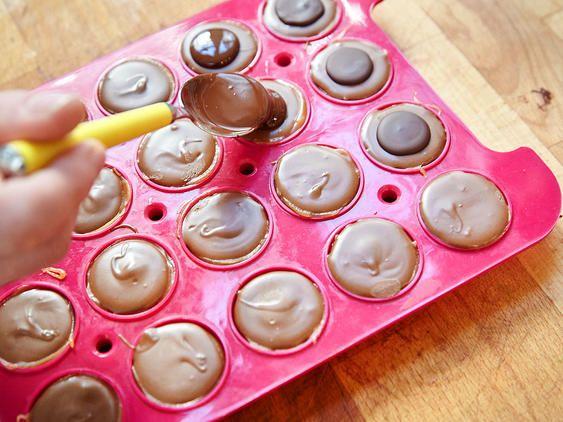 Geschmolzene Schokolade auf die Toffifees geben