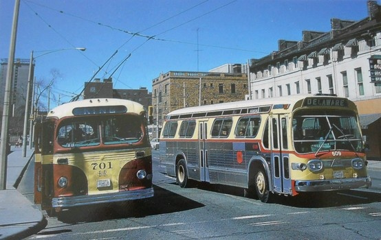 Hamilton Streeet Railway CanCar T-48 trolley coach 701 loads on Main Street at City Hall as diesel bus 609 hurries by, April 5, 1970. No. 701, the first new trolley acquired in 1950, would be retired in a few years as HSR renewed its electric fleet with buses from Flyer. No. 609 (model TDH-4517) was built by GM at Pontiac, Mich. in 1960 as part of a group of 12 buses which were active until the early 1980s. Photo by Ted Wickson