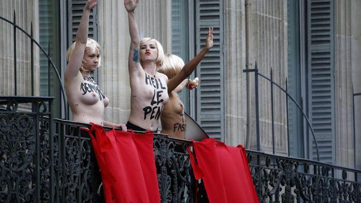 """Des femen interrompent le discours de Marine Le Pen en surgissant sur le balcon d'un hôtel place de l'Opéra. Elles font un salut nazi et accrochent des banderoles où est inscrit : """"Heil Le Pen""""   KENZO TRIBOUILLARD / AFP"""