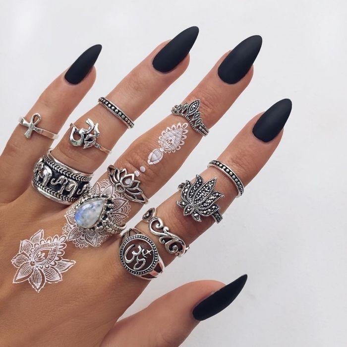 Weiße Henna Tattoos an der Hand, viele silberne Ringe, schwarzer Nagellack
