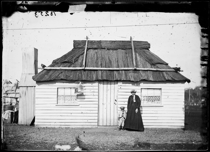 Mother and boy outside weatherboard house with bark roof, Gulgong