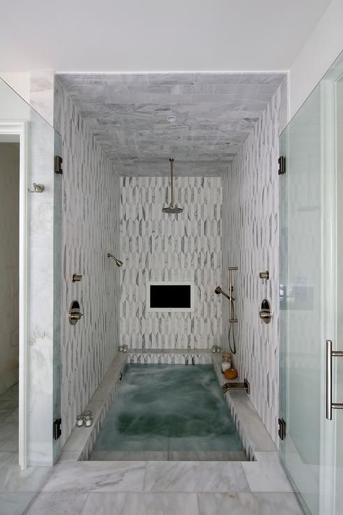 Stunning spa shower boasts white and gray marble tiles and ceiling fitted with a built in TV and a circular rain shower head and sprayer aimed over a sunken bathtub with steps leading out through double glass doors to white marble floors.