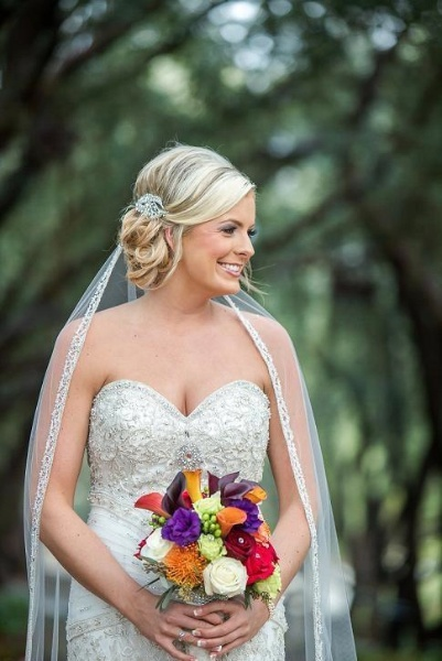 low side bun loose wave sparkly wedding dress blonde bride pretty makeup long veil up do hair trees