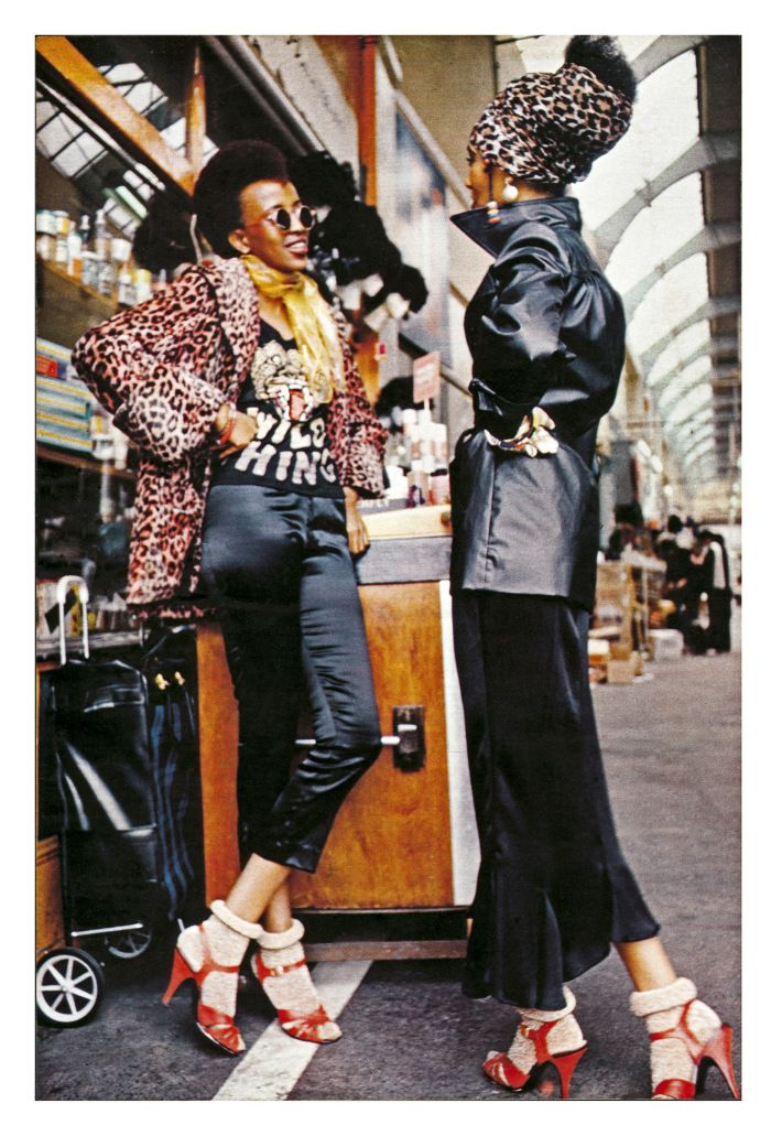 Two women at Brixton Market, London, 1973. Photo by Armet Francis 70s does 60s hot rod rockabilly style retro repro pencil cigarette pants black satin jacket platform shoes bobby socks street fashion