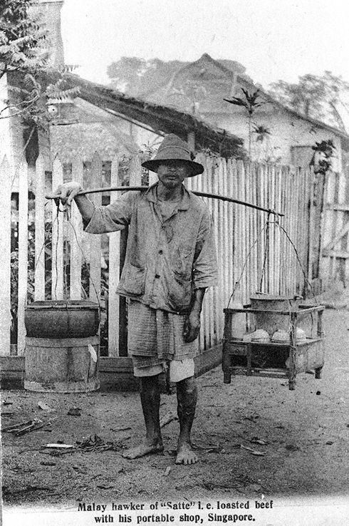MALAY HAWKER WITH HIS PORTABLE SHOP SELLING SATAY, SINGAPORE |  c.1907