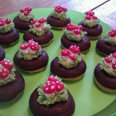 Mini chocolade donuts versieren met marsepein. Maak gras door wat marsepein door de knoflookpers te doen. Paddestoeltje is wit en rood bolletje marsepein met stippen van eetbare suikerstift.