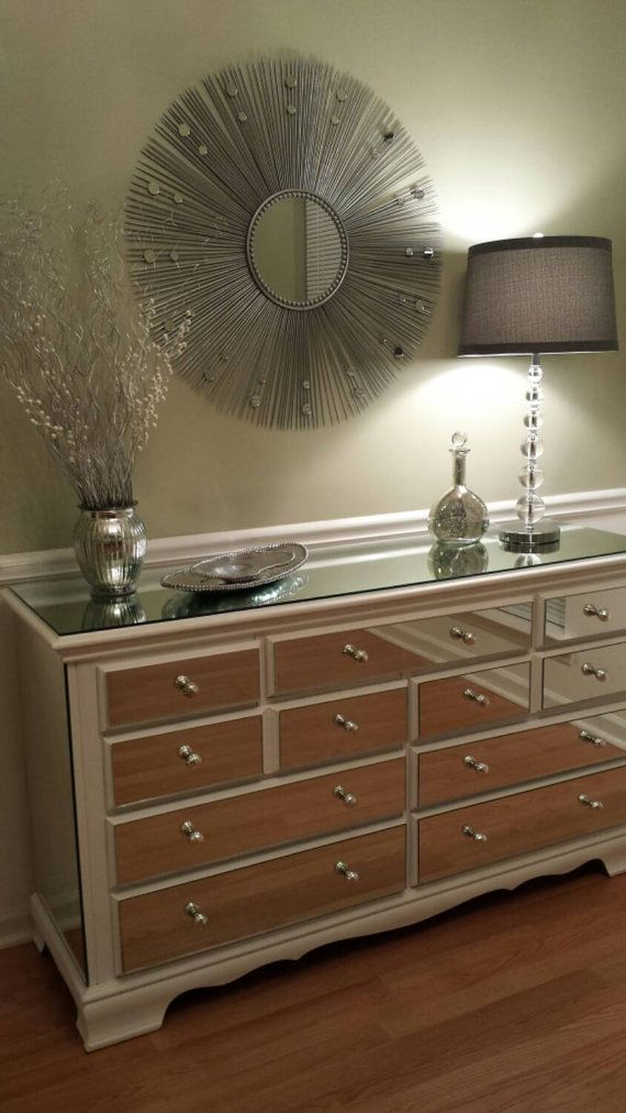This elegant 9 drawer dresser has been refinished to showcase 14 custom cut mirrors making it a sophisticated focal piece in any home. This piece,