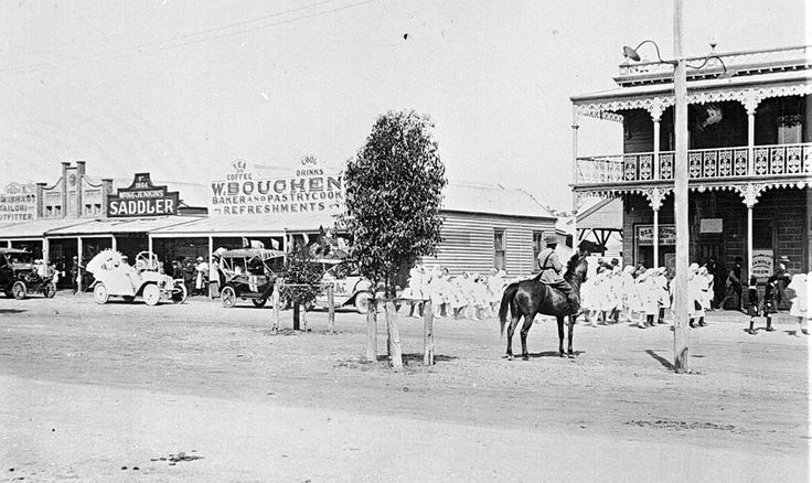 The main street in Rainbow. A parade of children followed by a number of motor cars, soldier on horseback watches the parade. Jenkins saddlers, W. Bouchen's pastrycook and a hotel are in the background.