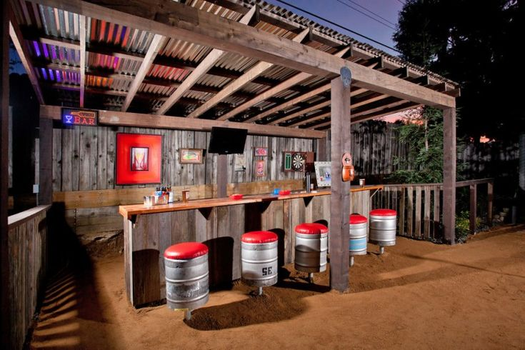 Rustic Wooden Outdoor Wet Bar With Stools Made Of Silver Barrel With Red  Pillows And Red