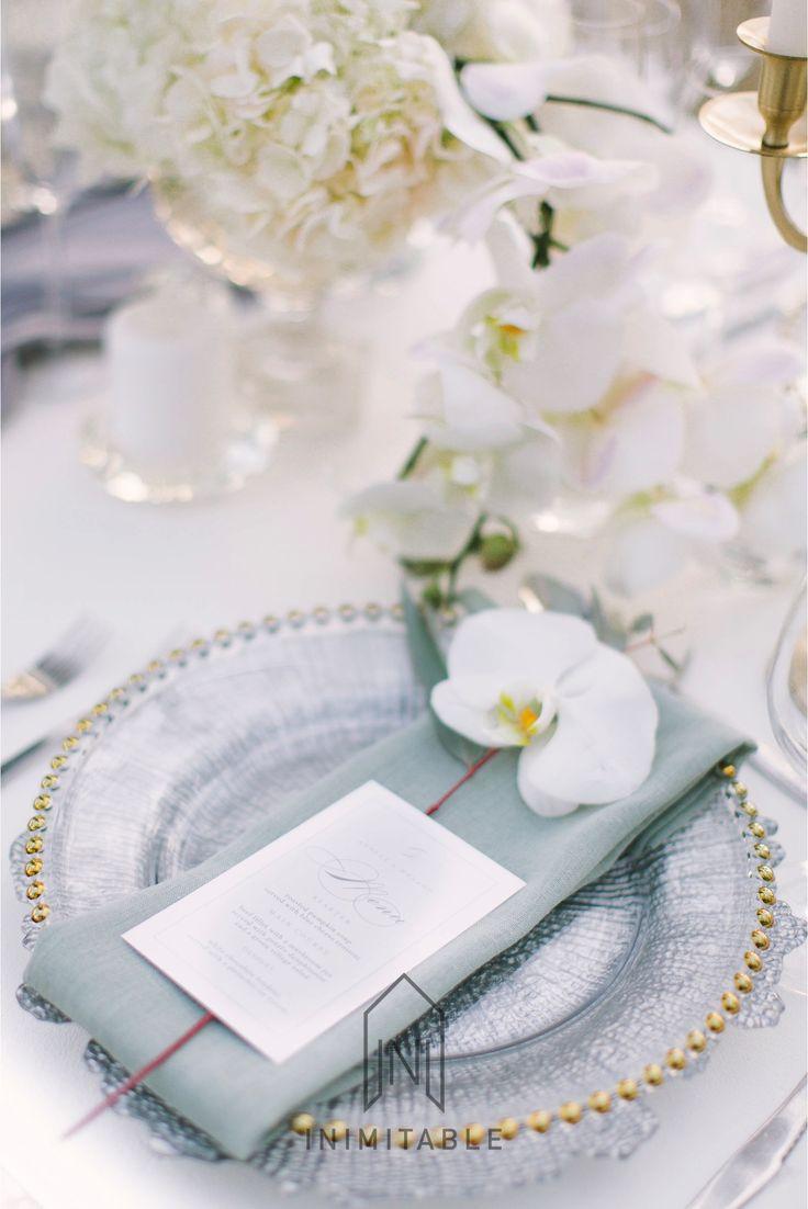 Inimitable Wedding Venue. Photography: @genevieve_fundaro  Hair and Make-up: @refinerythe  Dress: @calegrabridal  Floral Design: @zavionkotzeeventscompany  Venue: @inimitable_wv   #luxury #luxuryvenue #luxeweddings #luxewedding #flowerwall #allwhite #bride #bridal #floraldesign #bouquet. White and green flowers, gold under plates, grey, orchids, roses, elegant wedding table.
