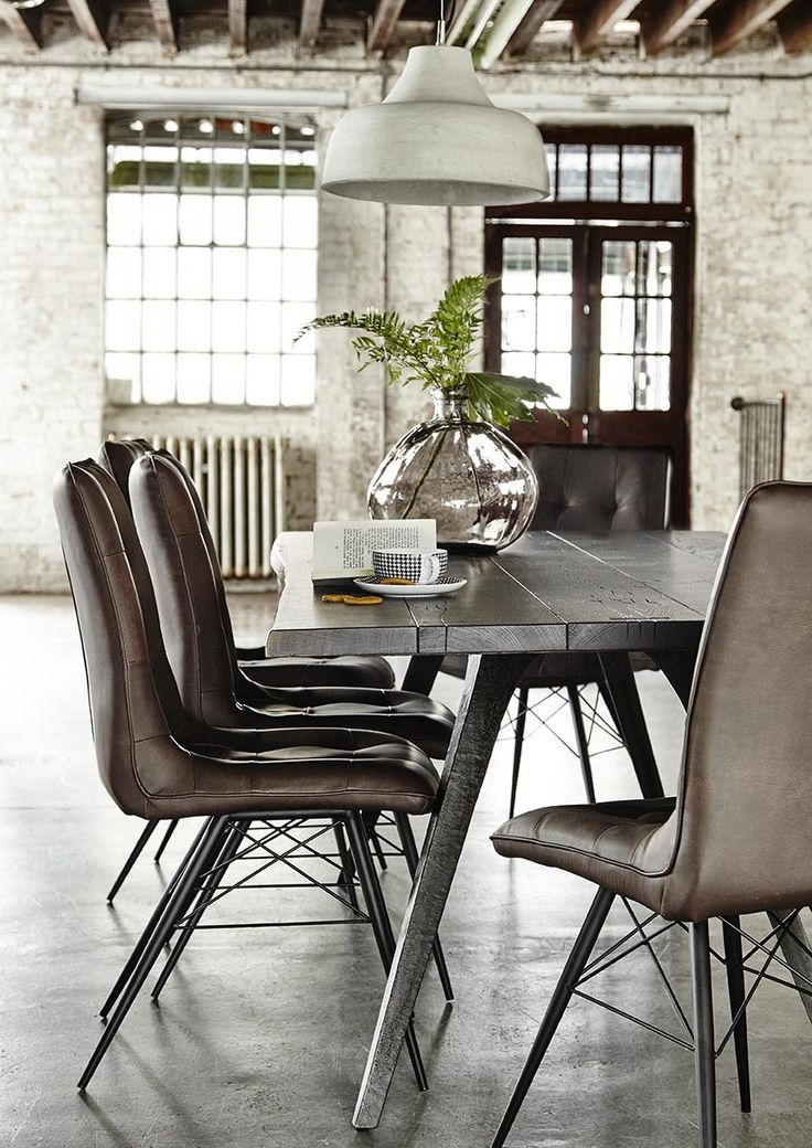 Beautiful Dining Room Setup With Concrete Floors Leather Chairs Brick Walls Exposed Wooden Beams And A Rustic Table