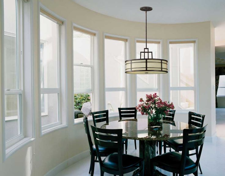 Incredible Light Fixtures with clear glass paneled single hung windows and round marble table including black leather padded chairs under shaded