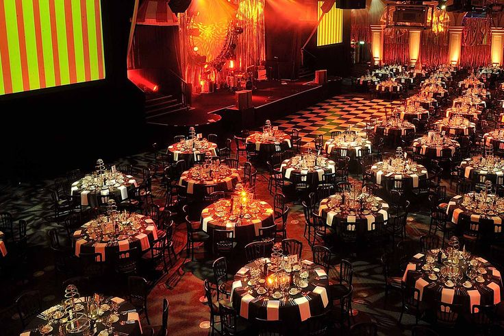 The vast interior of Old Billingsgate complete with black and white themed decoration and red lighting for a corporate Christmas party #CorporateChristmasParties #LondonVenues #CorporateEvents #OldBillingsgate