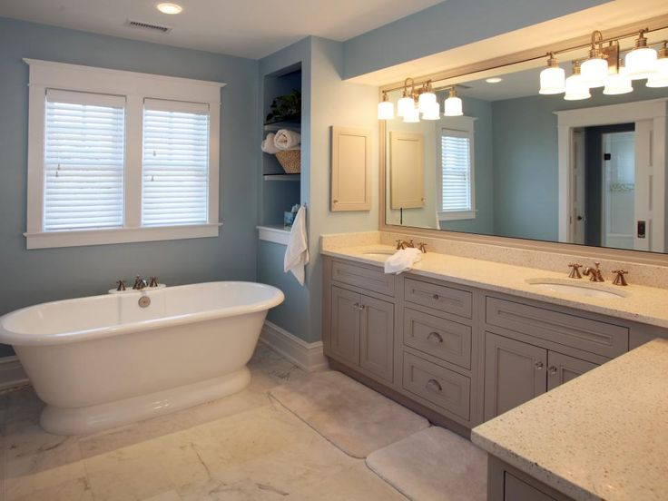 Soothing blue walls appear to recede, making this coastal-style bath appear larger. Built-in shelving takes advantage of an awkward corner next to the tub while a long double vanity provides ample counter space.