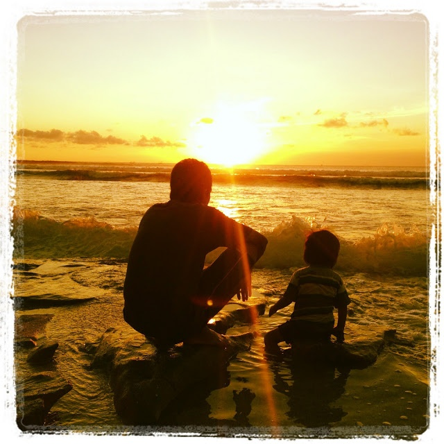 Father and Son spending precious time together watching the sun go down on Balangan Beach - Bali.