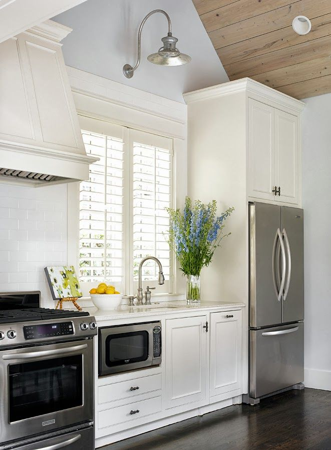 guest suite kitchen with full size fridge, stove and microwave. Like the kitchen window centered, the tall ceilings. The light fixture above window. Art on counters. Flowers. A small space but still gorgeous and perfect.